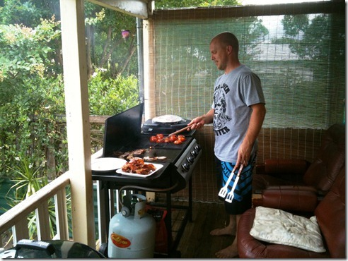 Sanna's cousin Nick cooking bacon and tomato's outside on the barbie